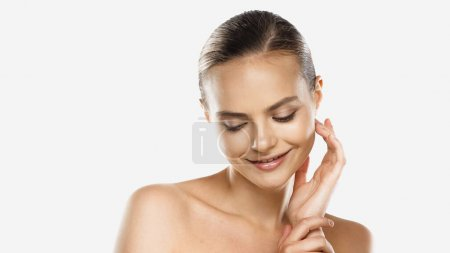 happy young woman with naked shoulders looking down isolated on white