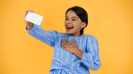 szczęśliwy nastolatek dziecko biorąc selfie na smartfon podczas śmiechu odizolowany na żółty