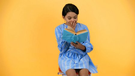amazed schoolgirl in blue dress reading book while sitting isolated on yellow
