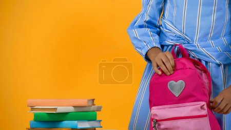 cropped view of schoolgirl holding backpack near books isolated on yellow