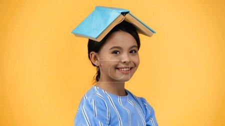 Photo pour Enfant heureux avec livre sur la tête souriant isolé sur jaune - image libre de droit