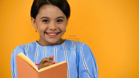 Photo for Cheerful kid holding pencil and notebook isolated on yellow - Royalty Free Image