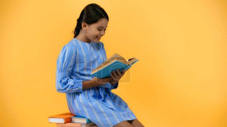 happy schoolgirl in blue dress reading book while sitting on yellow