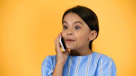 amazed preteen child talking on smartphone isolated on yellow