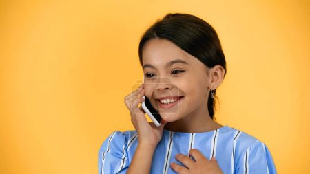 happy preteen child talking on smartphone isolated on yellow