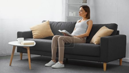 dreamy, pregnant woman looking away while sitting on couch with book