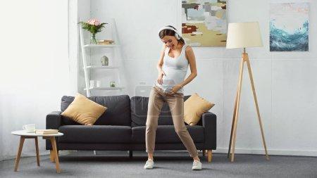 Ansicht der aufgeregten Schwangeren mit Smartphone beim Tanzen im Kopfhörer in voller Länge