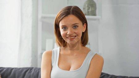 young, pretty woman smiling at camera at home