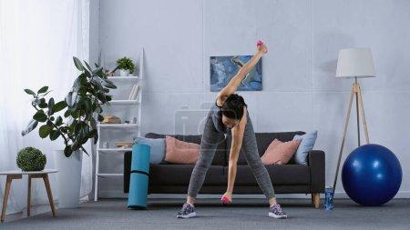 Photo pour Jeune femme en vêtements de sport travaillant avec des haltères à la maison - image libre de droit