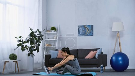 Photo for Young woman in sportswear working out on fitness mat at home - Royalty Free Image