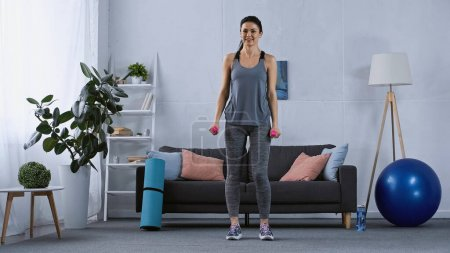 Photo for Young woman in sportswear exercising with dumbbells at home - Royalty Free Image