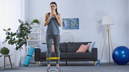 Photo for Young woman in sportswear working out with resistance band at home - Royalty Free Image