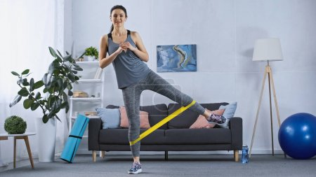Photo for Young woman in sportswear working out with elastics at home - Royalty Free Image