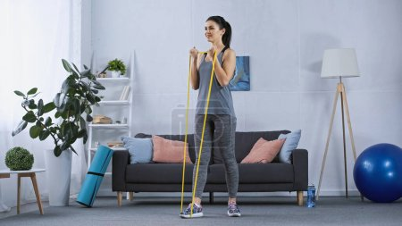 Photo for Happy young woman in sportswear working out with elastics at home - Royalty Free Image