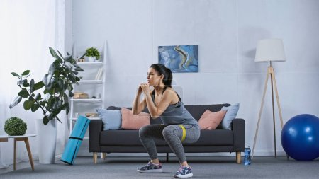 Photo for Young woman in sportswear exercising with resistance band at home - Royalty Free Image