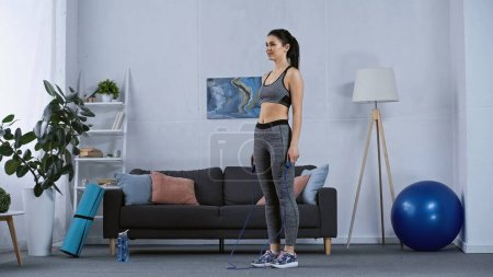 Photo for Young woman in sportswear working out with jumping rope at home - Royalty Free Image