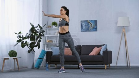 Photo for Young brunette woman in sportswear working out at home - Royalty Free Image