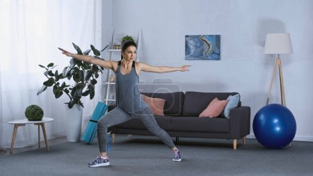 Photo for Young brunette woman in sportswear exercising at home - Royalty Free Image