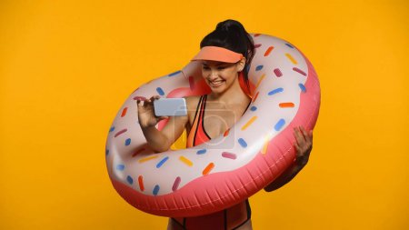 Photo for Cheerful young woman in swimsuit and inflatable ring taking selfie isolated on yellow - Royalty Free Image