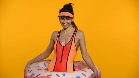 Cheerful young woman in swimsuit and inflatable ring isolated on yellow