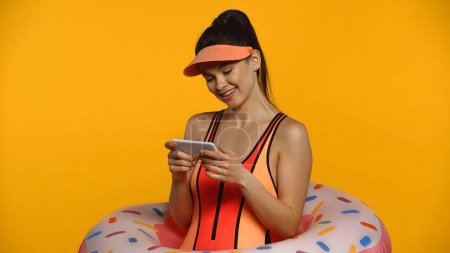 Photo for Cheerful young woman in swimsuit and inflatable ring using smartphone isolated on yellow - Royalty Free Image