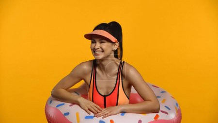 Cheerful young woman in swimsuit and inflatable ring smiling isolated on yellow