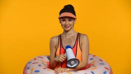 Fröhliche junge Frau in Badeanzug und aufblasbarem Ring mit Megafon in der Hand