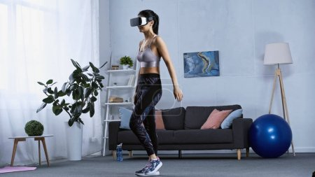 Photo for Happy young woman in sportswear and vr headset working out at home - Royalty Free Image