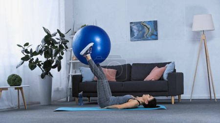 young brunette sportswoman exercising with fitness ball at home