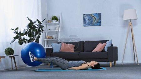 junge brünette Sportlerin trainiert zu Hause mit Fitnessball auf Matte