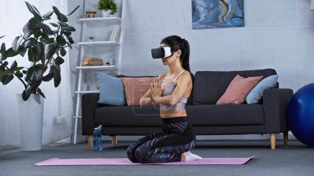 Photo for Young woman in sportswear and vr headset sitting on fitness mat while working out at home - Royalty Free Image