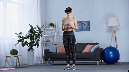 Photo for Young woman in sportswear and vr headset standing in modern living room - Royalty Free Image