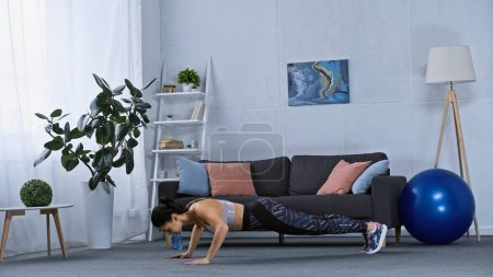 Photo for Young woman in sportswear doing plank exercise at home - Royalty Free Image