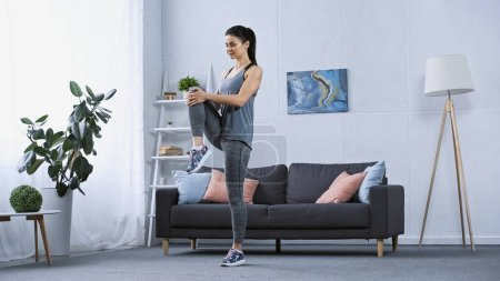 young brunette woman in sportswear working out at home