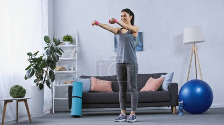 Photo for Happy young woman in sportswear exercising with dumbbells in modern living room - Royalty Free Image
