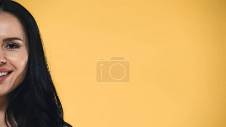 partial view of cheerful brunette woman looking at camera isolated on yellow