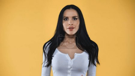 astonished brunette woman looking at camera isolated on yellow