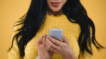 partial view of brunette woman messaging on mobile phone isolated on yellow