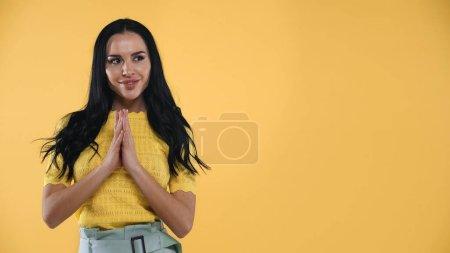 Photo pour Femme brune positive debout avec les mains priantes isolé sur jaune - image libre de droit
