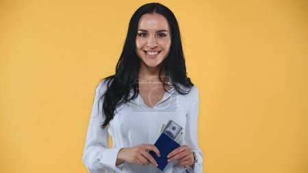young, happy businesswoman holding passport, air ticket and money isolated on yellow