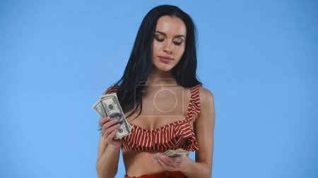 pretty, brunette woman in swimsuit counting dollar banknotes isolated on blue