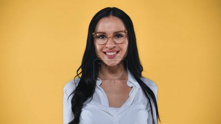 joyful businesswoman in eyeglasses smiling at camera isolated on yellow