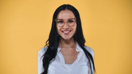 joyful businesswoman in eyeglasses smiling at camera isolated on yellow
