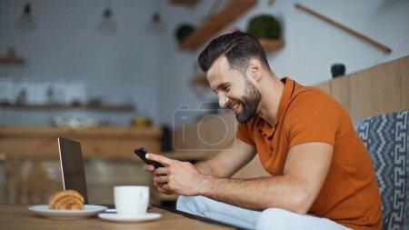 Photo pour Message freelance heureux sur smartphone près d'un ordinateur portable et petit déjeuner dans le café - image libre de droit