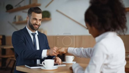 Photo for Happy businessman shaking hands with with african american partner in cafe - Royalty Free Image