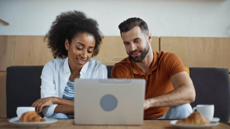 cheerful interracial freelancers looking at laptop and breakfast in cafe