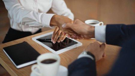 Photo pour Vue recadrée de partenaires d'affaires multiethniques serrant la main lors d'une réunion dans un café - image libre de droit