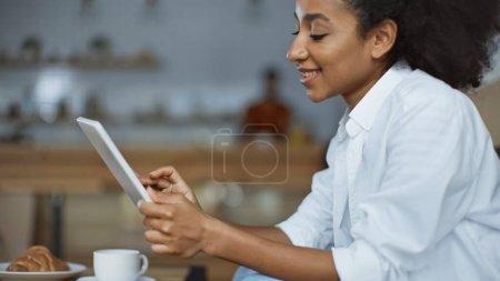 Photo pour Femme afro-américaine gaie utilisant une tablette numérique - image libre de droit