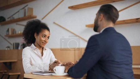 positive african american businesswoman talking with blurred partner during meeting in cafe