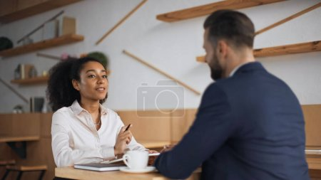 interracial business partners talking during meeting in cafe